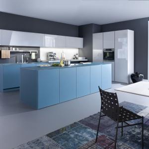 Białe błyszczące fronty mebli kuchennych idealnie pasują do dolnej zabudowy i wyspy wykończonej jasnym, niebieskim kolorem. Fot. Leicht.