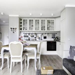 Umowną granicę pomiędzy aneksem kuchennym a salonem wyznacza niewielka jadalnia dla czterech osób. Otwartą strefę dzienną wizualnie spaja jednorodna, drewniana podłoga oraz szare ściany w kuchni i salonie. Projekt: Decoroom. Fot. Ayuko Studio.