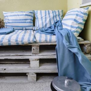 Latem właścicielka relaksuje się na balkonie. Tutaj rolę mebli wypoczynkowych pełnią drewniane palety wyłożone poduszkami. Projekt: Decoroom. Fot. Ayuko Studio.