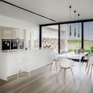 W tej nowoczesnej kuchni dużą, białą wyspę kuchenną zestawiono z wysoką zabudową, której wykończone na wysoki połysk fronty mają kolor kawy z mlekiem. Fot. Zajc Kuchnie, model Z1.