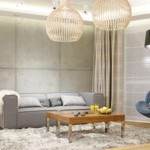 W nowoczesnym salonie zdecydowano się na sofę 2,5-osobową w szarym kolorze. Doskonale współgra ona z betonową ścianą. Projekt: Agnieszka Hajdas-Obajtek. Fot. Bartosz Jarosz.