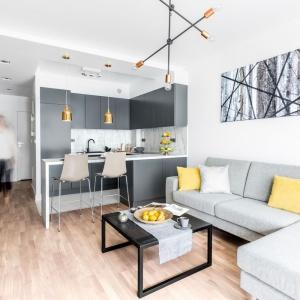 W mieszkaniu króluje szarość, udekorowana złotymi detalami oraz okraszona geometrycznymi motywami. Ciekawy efekt osiągnięto poprzez duplikację formy lampy w salonie w postaci grafiki na ścianie. Projekt: Decoroom.