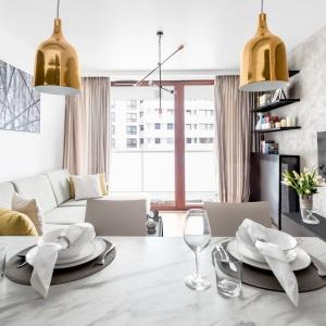 Strefę wypoczynku w salonie tworzy elegancki, jasnoszary narożnik oraz minimalistyczny stolik kawowy zwrócone w kierunku zamontowanego na ścianie TV. Projekt: Decoroom.