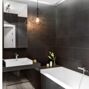 Geometryczna lampa w industrialnym stylu jest najistotniejszym elementem dekoracyjnym łazienki. Projekt: Decoroom.