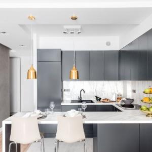 Zabudowa kuchenna kontynuuje kolorystykę zapoczątkowaną przez ściany. Fronty mebli kuchennych są ciemnoszare, przełamane jasnym blatem i ścianą nad blatem, wyłożoną pięknymi płytkami o strukturze polerowanego marmuru. Projekt: Decoroom.