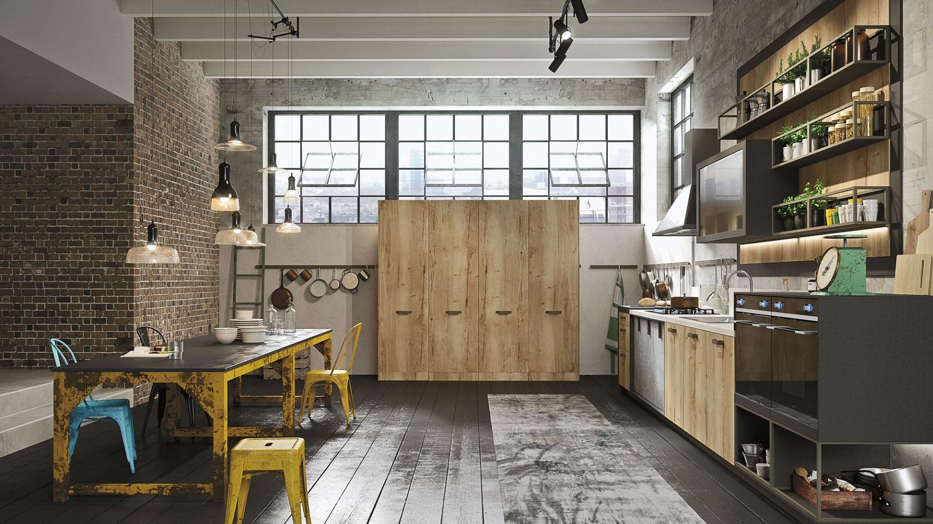 W przestronnej loftowej przestrzeni klimat buduje nie tylko cegła na ścianie czy odkryte belki stropowe, ale przede wszystkim zabudowa kuchenna i część jadalniana. Stołki i nogi stołu są kolorowe, z poobdzieraną częściowo farbą. Fot. Snaidero, kuchnia Loft.