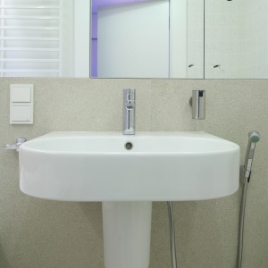 Lustrzane szafki umieszczone nad umywalką zapewniają sporo miejsce na przechowywanie. Optycznie powiększają również wnętrze łazienki. Projekt: Kasia i Michał Dudko. Fot. Bartosz Jarosz.