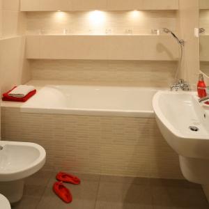 Chociaż metraż łazienki jest mały, zmieściła się w niej wygodna wanna. Wokół niej oraz nad nią zostały wykonane półki, na których można ustawiać kosmetyki. Łazienka wydaje się dużo większa niż jest w rzeczywistości. Taki efekt daje jasna kolorystyka oraz liczne lampki. Przestrzeń powiększa również duże lustro nad umywalką. Projekt: właściciele. Fot. Bartosz Jarosz.
