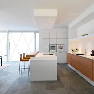 Przestronna kuchnia z długim blatem i pojemną dolną zabudową została również wyposażona w dużą wyspę, pełniącą funkcję strefy gotowania i baru oraz wysoką zabudowę, chowającą się w ścianie. Jej obecność jest bardziej widoczna jedynie za sprawą wykończenia na wysoki połysk oraz sprzętów AGD w nią wkomponowanych. Fot. Leicht. Projekt: Henning Baurmann.