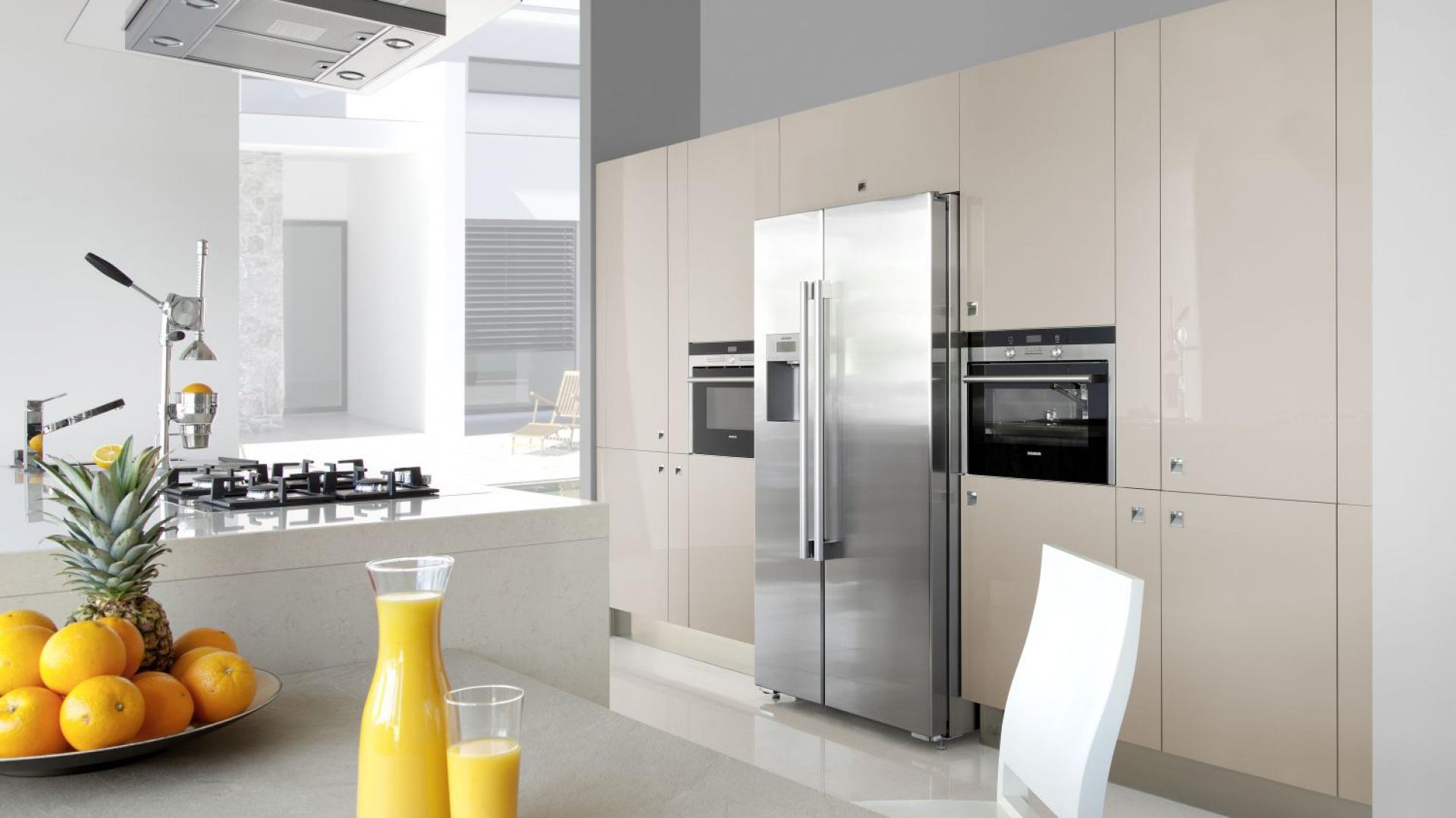 Wysoka zabudowa kuchenna wykończona w wysokim połysku i delikatnym beżowym kolorze zdaje się otulać stalową lodówkę typu side-by-side. Znalazło się również miejsce na inne sprzęty AGD. Fot. WFM Kuchnie, kuchnia Riflesso Spizzare.
