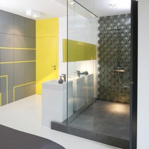 Kabina z sauną są wyspą w tym pomieszczeniu. Umywalki umieszczono przy szklanej ścianie, dzięki czemu wyróżniają się i wysuwają na widoczny plan. Fot. Bartosz Jarosz.