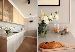 Szary kolor na ścianach został powtórzony na lakierowanych frontach meblowych w kuchni tak by zabudowa meblowa stanowiła integralny element wnętrza.