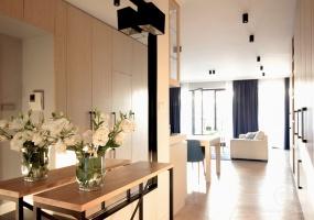 Na wejściu do mieszkania zaprojektowane zostało duże lustro w czarnej ramie i konsola. Całości smaczku dodają kinkiety zamontowane w lustrze.