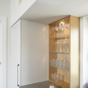 Otwarte szafki w kolorze ciepłego drewna ocieplają chłodną w odbiorze biel. Projekt: Kamila Paszkiewicz. Fot. Bartosz Jarosz.