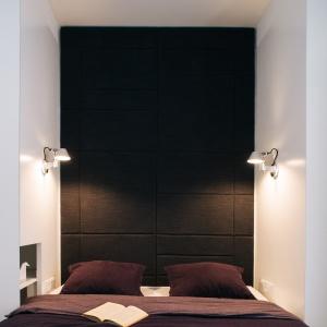 Sypialnia zyskała przytulny charakter dzięki tapicerowanemu zagłówkowi, poprowadzonemu wzdłuż wysokości całej ściany aż do sufitu. Projekt:81.WAW.PL. Fot. Rafał Kłos.
