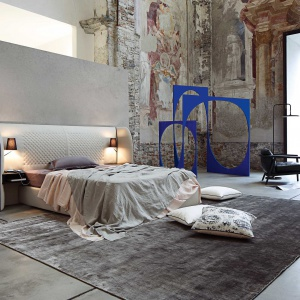 Ekskluzywne łóżko Cherchemidi ma ogromny, tapicerowany zagłówek, który zaokrągla się w stronę miejsca spania. To przytulny azyl do spania oraz przechowywania, bowiem do zagłówka przymocowane są półeczki. Fot. Roche Boibos.