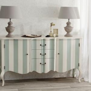 Stylowa, drewniana komoda Juliet w stylu francuskim z 3 szufladami i 2 drzwi. Wykonana ręcznie z egzotycznego drewna pomalowanego na biało. Idealna do salonu lub jadalni. Fot. Dekoria.