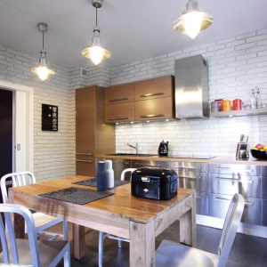 Kuchnię w tym warszawskim apartamencie urządzono w industrialnej stylistyce. Królują metal i cegła. Tym razem w białej odsłonie, dzięki czemu spokojnie można było wykończyć nią duże powierzchnie ścian bez efektu przytłoczenia pomieszczenia. Projekt i zdjęcia: Soma Architekci.
