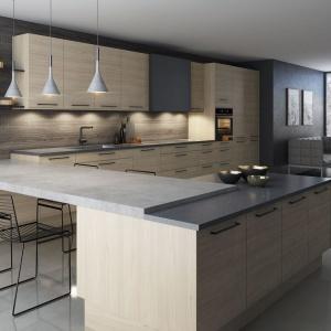 Modne połączenie szarości z beżami, zamknięte w proste, nowoczesne kształty i rysunek drewna. Całości dopełniają otwarte półki, będące przedłużeniem wysokiej zabudowy. Fot. Sigdal, model Nordisk.