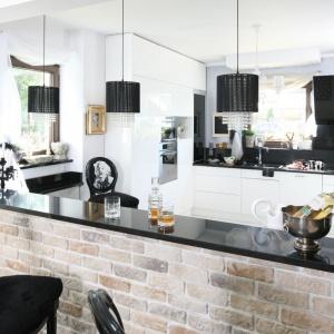 Czarno-białą kuchnię w stylu glamour zamyka od strony jadalni barek, który wykończono czerwoną cegłą. Projekt: Magdalena Konochowicz. Fot. Bartosz Jarosz.