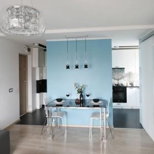 Cała przestrzeń została spójnie zaprojektowana, zarówno pod względem zastosowanej kolorystyki, jak i materiałów wykończeniowych. Powiększająca przestrzeń biel, lakierowane powierzchnie oraz lustrzana ściana dodają strefie dziennej kilka metrów kwadratowych. Projekt: Marta Kilan. Fot. Bartosz Jarosz.