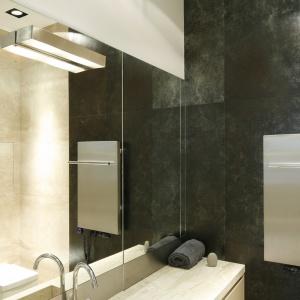 Duże lustra powiększają łazienkę. Za jednym z nich jest ukryta szafka. Powierzchnia: ok. 4 m². Projekt: Iza Mildner. Fot. Bartosz Jarosz.