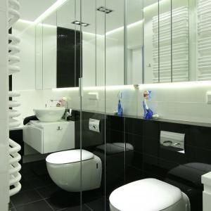 Lustra od podłogi do sufitu skrywają domową pralnię oraz schowek. Odbicie w wiszących szafkach lustrzanych powiększa optycznie małą łazienkę. Fot. Bartosz Jarosz.