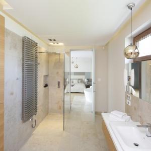 Łazienka łączy się z sypialnią. Pomieszczenia oddzielają szklane drzwi. Fot. Bartosz Jarosz.