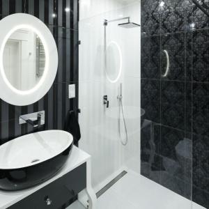 Wrażenie jakie robi aranżacja łazienki to m.in. efekt połączenia różnych motywów dekoracyjnych: płytki wpasy wstrefie umywalki oraz zwyszukanym, tkaninowym wzorem wstrefie prysznica. Projekt: Katarzyna Mikulska-Sękalska. Fot. Bartosz Jarosz.