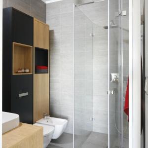 Pozornie mała łazienka nabrała przestrzeni dzięki przeszklonej kabinie prysznicowej. Meble łączące wsobie dekor dębowego drewna iczarne wstawki wniosły elegancki klimat. Projekt: Małgorzata Łyszczarz. Fot. Bartosz Jarosz.