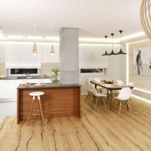 W tej kuchni drewno jest obecne zarówno w powierzchniach pionowych, jak i poziomych. Podłogę wykonano z pięknych, olejowanych dębowych desek. Projekt: Agnieszka Hajdas-Obajtek. Fot. Bartosz Jarosz.