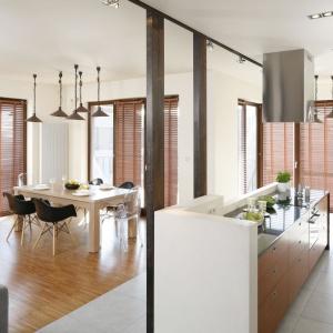 Mieszkanie urządzono w stylu industrialnym z odsłoniętymi belkami stropowymi, co z kolei zaowocowało świetną okazją do wykorzystania stalowych kolumn jako elementu działowego pomiędzy kuchnią i salonem z jadalnią. Projekt: Marta Kruk. Fot. Bartosz Jarosz.