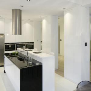 Biało-czarną, elegancką kuchnię od strony salonu przesłaniają trzy kolumny, które pozwalają utrzymać niezależność poszczególnych przestrzeni przy jednoczesnym ich otwarciu. Projekt: Katarzyna Mikulska-Sękalska. Fot. Bartosz Jarosz.