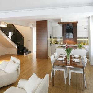 Jadalnia pełni również funkcję przestrzeni oddzielającej wyraźnie kuchnię od salonu oraz spajającej obydwa pomieszczenia wizualnie. Projekt: Kamila Paszkiewicz. Fot. Bartosz Jarosz.
