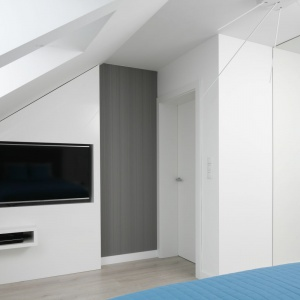 W sypialni znalazło się miejsce dla ściany z telewizorem, który został dyskretnie wpasowany w biały panel, nie zaburzając delikatnej aranżacji pomieszczenia. Projekt: Marta Kilan. Fot. Bartosz Jarosz.
