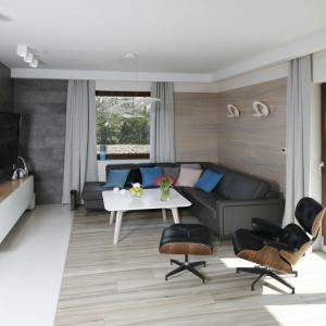 Towarzyszący urządzaniu wnętrza pragmatyzm zaowocował wykorzystaniem w salonie forniru i okładziny kamiennej. Naturalne materiały zbudowały w pomieszczeniu przytulny, domowy klimat. Projekt: Marta Kilan. Fot. Bartosz Jarosz.