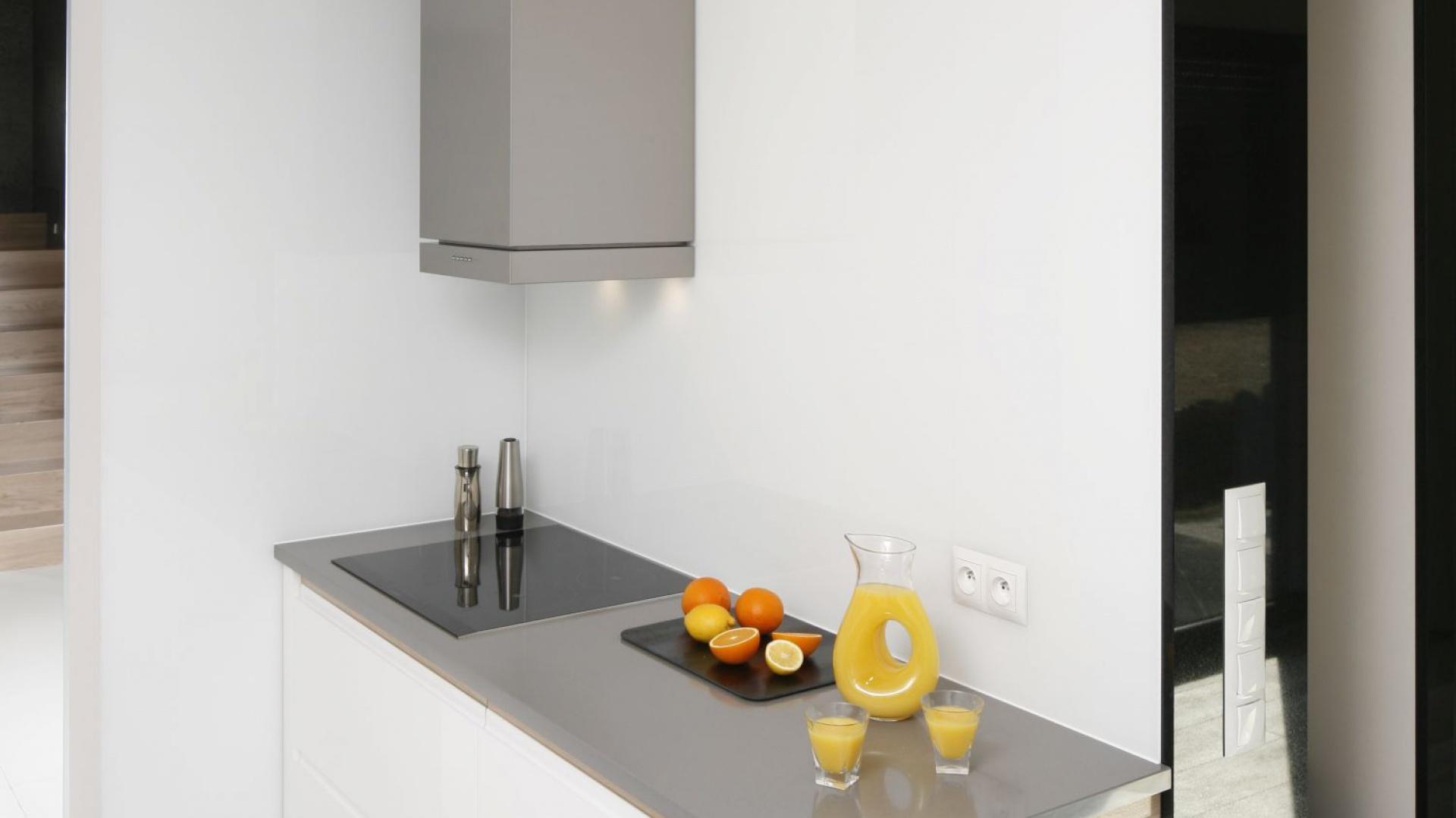 Dominującą w przestrzeni kuchni biel przełamano ocieplającym ją wizualnie drewnem dębowym oraz szarym, konglomeratowym blatem. Projekt: Marta Kilan. Fot. Bartosz Jarosz.