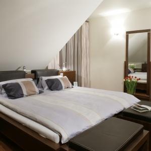 Podwójna tapicerowana ławka sprawi, że małżeńska sypialnia stanie się ciekawsza i bardziej wygodna w użytkowaniu dwóch osób - dzięki niej zyskujemy miejsce do odłożenia narzuty czy szlafroka. Projekt: Jacek Radulski. Fot. Bartosz Jarosz.