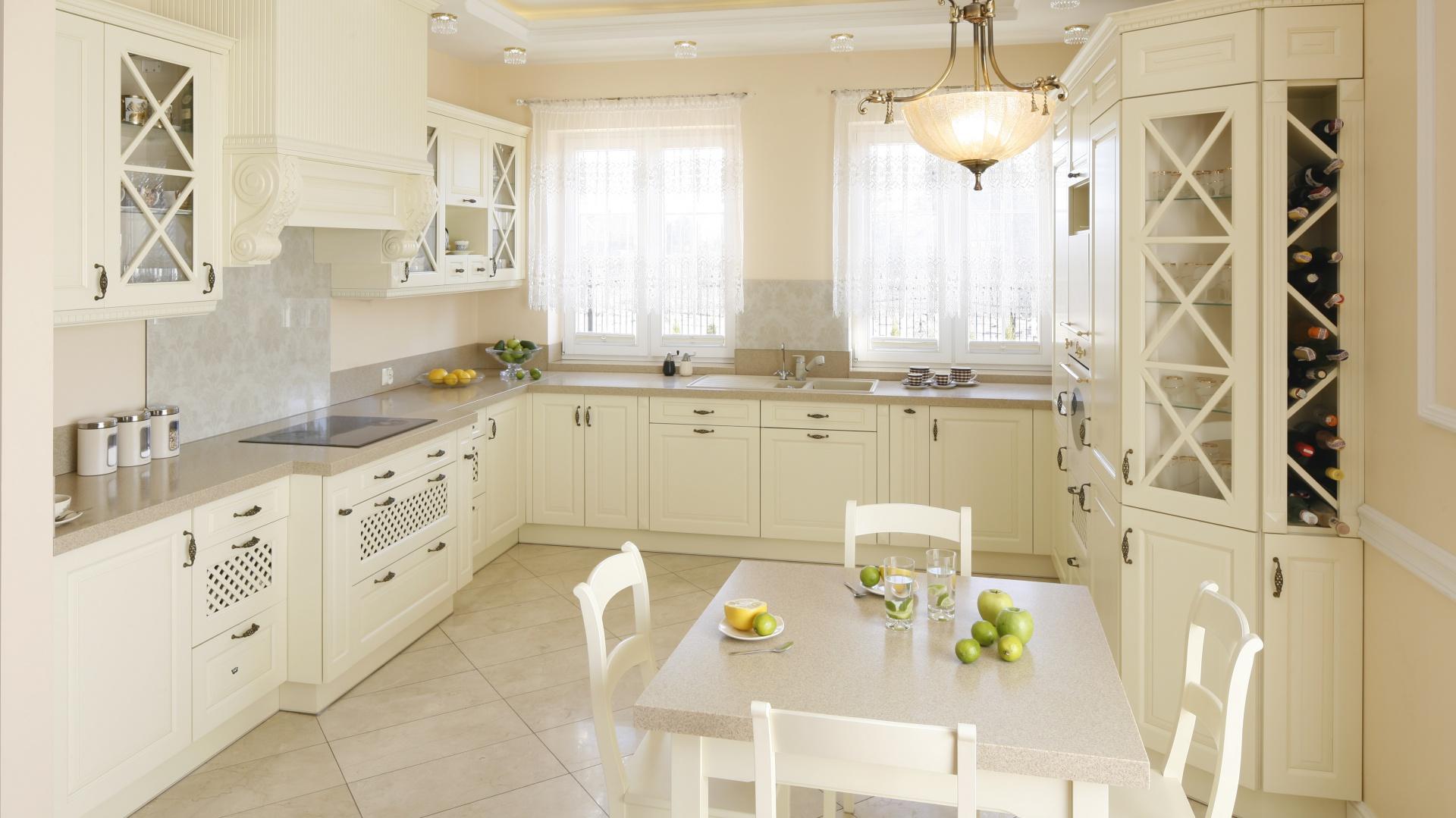 Piękna kuchnia w angielskim stylu zdominowana całkowicie przez kolor złamanej bieli. Meble są zdobne, stylizowane, licznie udekorowane ażurowymi prześwitami, szprosami i kutymi uchwytami. Projekt: Magdalena Mirek-Roszkowska. Fot. Bartosz Jarosz.