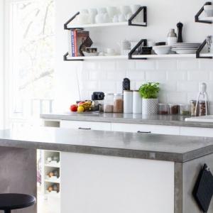 Blat kuchenny wykonany z prawdziwego betonu wieńczy dolną zabudowę i wyspę w tej skandynawskiej kuchni. Fot. Morgan&Moeller.