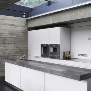 W tej kuchni urządzonej w stylu loft postawiono na beton. Nie tylko widoczny jest na ścianach pomieszczenia, ale także w formie laminowanego blatu kuchennego imitującego ten materiał. Fot. Pfleiderer, blat Urban Concrete.