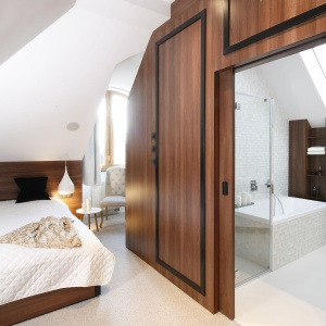 Główna sypialnia połączona jest złazienką: pomieszczenia oddzielają przesuwane drzwi wykończone fornirem orzecha amerykańskiego ujęte wformę imponującej ramy. Projekt: Jan Sikora. Fot. Bartosz Jarosz.