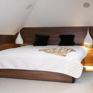 Przytulna izarazem elegancka sypialnia urządzona jest pod skosem dachowym. Kształt pomieszczenie oraz ciepłe forniry zapewniają przytulny klimat. Projekt: Jan Sikora. Fot. Bartosz Jarosz.