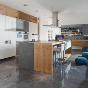 Nowoczesna kuchnia z bardzo dużą wyspą wykonaną z dwóch różnych materiałów i kolorów. Zestawienie surowej szarości z ciepłym drewnem prezentuje się bardzo efektownie. Z kolei lekko wysunięty blat pozwolić wykorzystać część wyspy jako barek śniadaniowy. Fot. Mebel Rust, kolekcja Avant-garde.