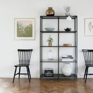 W holu mocnym akcentem kolorystycznym jest czarna szafka i towarzyszące jej czarne krzesła. Ich otwarta, ażurowa konstrukcja sprawia, że nie przytłaczają przestrzeni mimo ciemnej kolorystyki. Fot. Krister Engström.