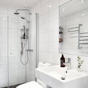 Biel dominuje również w przestrzeni łazienki. W kolorze tym utrzymano płytki na ścianach i ceramikę sanitarną. Z jej reżimu wyłamała się podłoga, wyłożona beżowo-brązową mozaiką. Fot. Krister Engström.