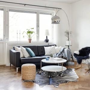 Wzrok przyciągają dekoracyjne detale: ciekawy stolik kawowy, wiklinowy puf oraz puchata narzuta na bujanym eamesowskim fotelu. Fot. Krister Engström.