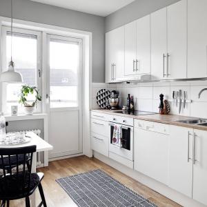 Białą zabudowę kuchenną wieńczy drewniany blat w przyjemnym, jasnym wybarwieniu. Ociepla on wizualnie przestrzeń kuchni i harmonizuje z podłogą. Fot. Krister Engström.