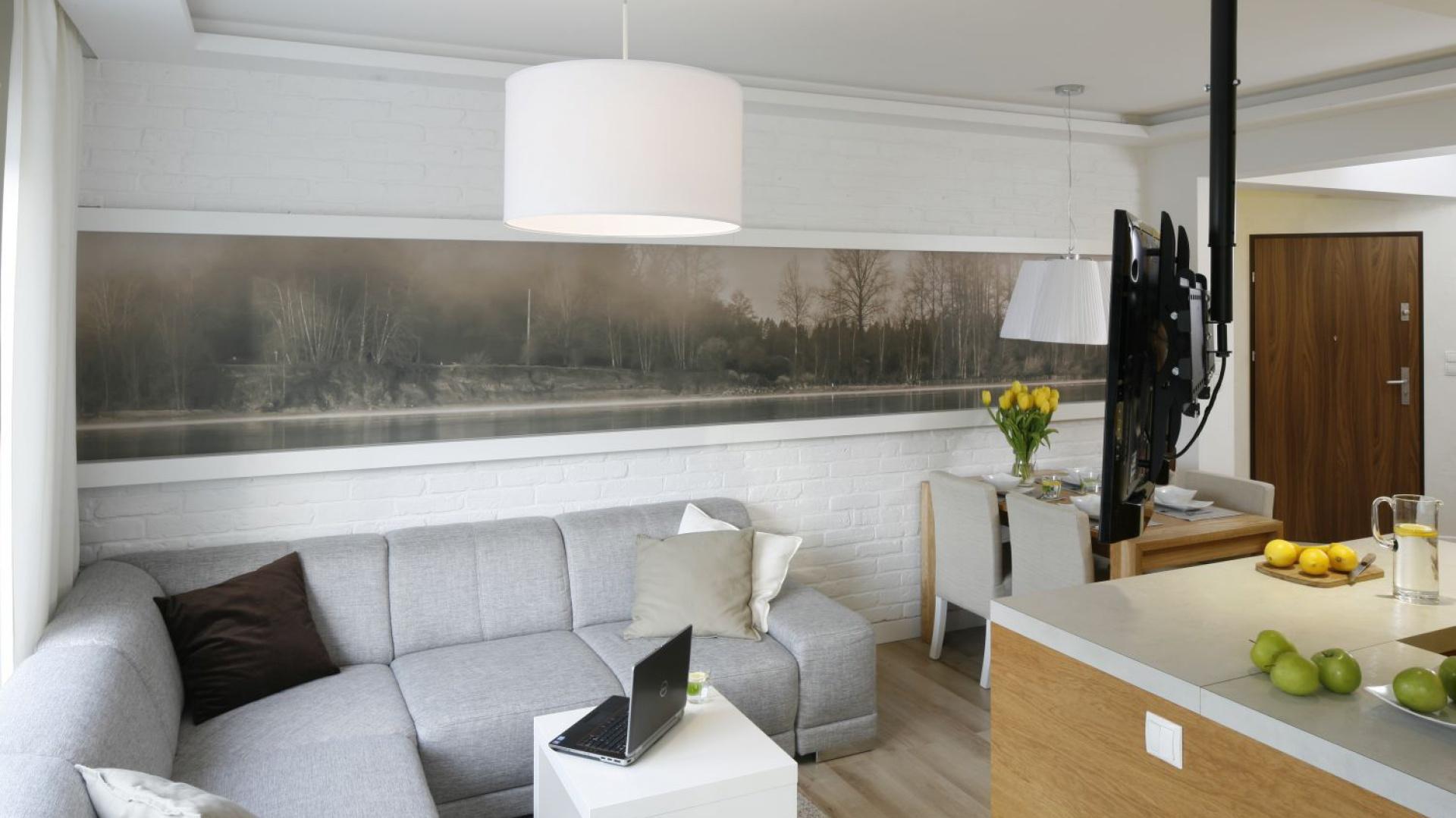 W otwartej strefie dziennej niedużą przestrzeń zdobi wykonany w sepii pejzaż. Pięknie prezentuje się on na ścianie wyłożonej białą cegłą. Projekt: Małgorzata Mazur. Fot. Bartosz Jarosz.