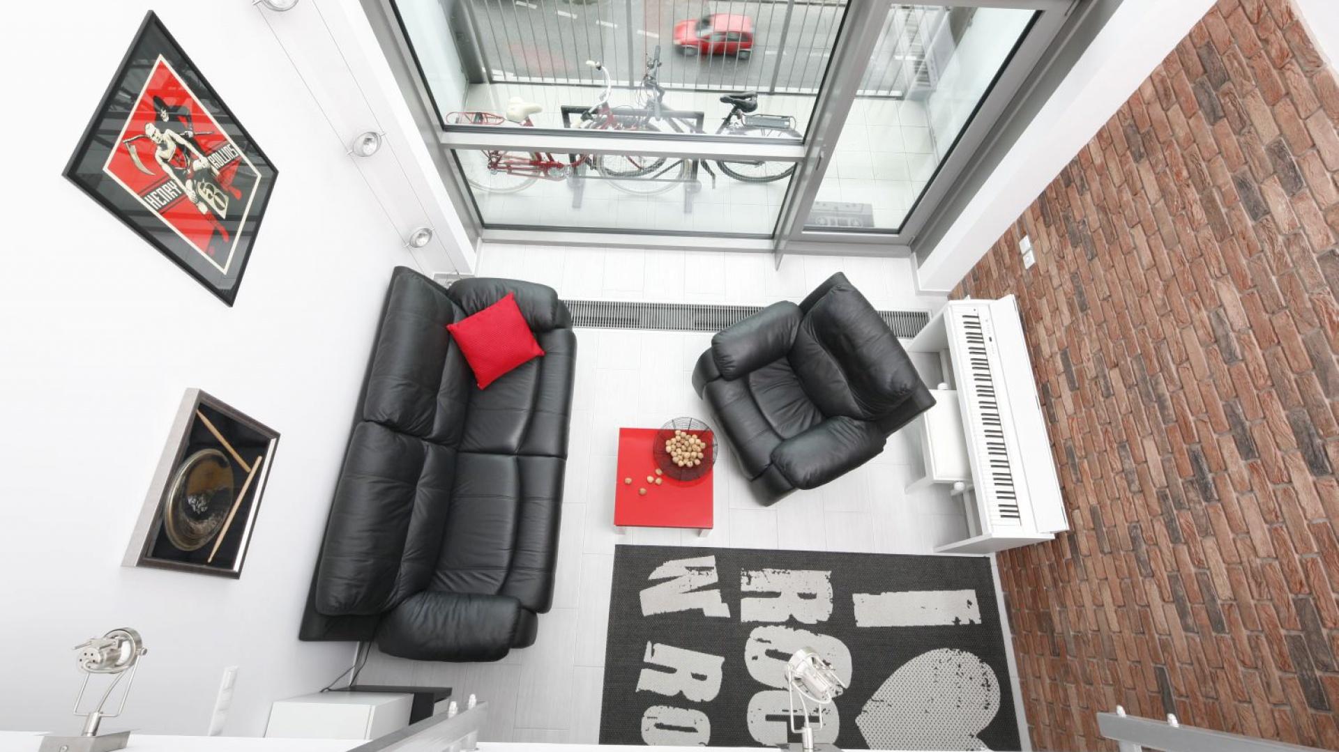 W niedużym apartamencie wrażenie przestronności buduje otwarta na antresolę przestrzeń. Czerwona cegła na ścianie podkreśla loftowy charakter aranżacji. Projekt: Monika Olejnik. Fot. Bartosz Jarosz.